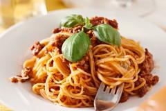 spaghetti with basil garnish in meat sauce